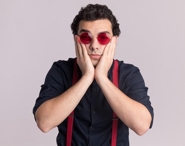 Uomo alla moda con il farfallino con gli occhiali e le bretelle guardando davanti preoccupato e confuso in piedi sopra il muro bianco
