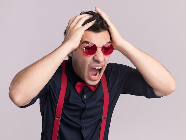 Uomo alla moda con farfallino che indossa occhiali e bretelle che grida con espressione aggressiva che si scatena con le mani sulla testa in piedi sopra il muro bianco