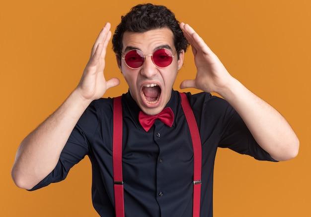 Uomo alla moda con il farfallino con gli occhiali e le bretelle che grida con le braccia alzate impazzendo in piedi sopra il muro arancione