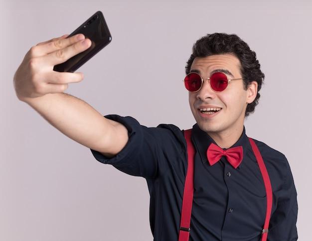 Uomo alla moda con il farfallino con gli occhiali e le bretelle utilizza lo smartphone facendo selfie sorridendo allegramente in piedi sopra il muro bianco