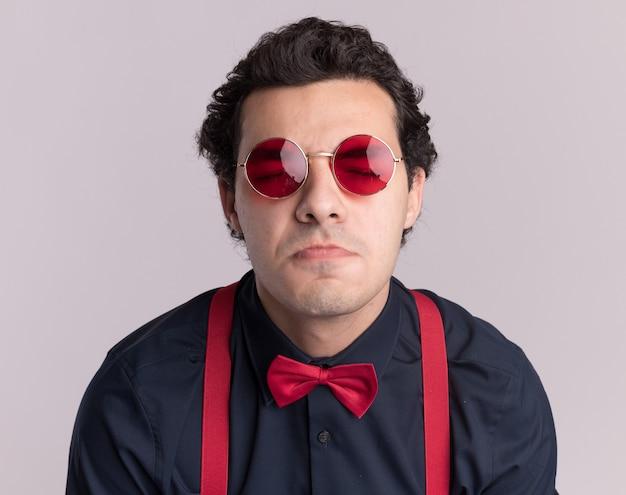 Uomo alla moda con farfallino che indossa occhiali e bretelle con gli occhi chiusi, increspando le labbra in piedi sopra il muro bianco