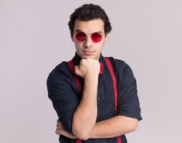 Uomo alla moda con farfallino che indossa occhiali e bretelle con il pugno sul mento guardando davanti con faccia seria in piedi sopra il muro bianco