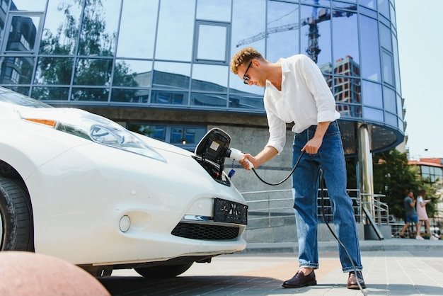 커피 컵을 손에 든 세련된 남자는 전기 자동차 충전 소켓에 플러그를 꽂습니다.