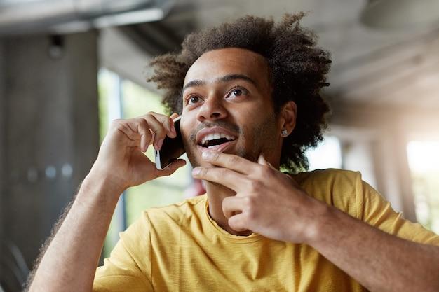 スマートフォンを介して彼の友人とチャットしながら、暗い肌と遠くを見ている巻き毛を持つスタイリッシュな男は神秘的な表情を持っています。
