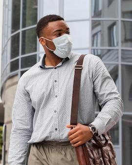 Стильный мужчина с маской для лица по пути на работу во время пандемии