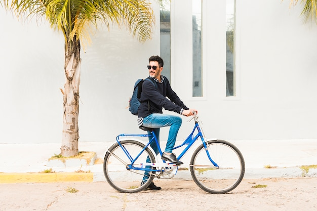 Stylish man with his backpack riding on blue bicycle