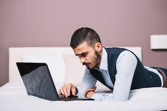 Stylish man with laptop posing on bed