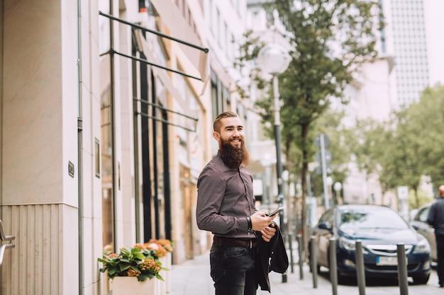 電話で長いひげを持つスタイリッシュな男