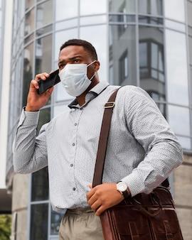 Uomo alla moda con la maschera mentre va al lavoro e parla al telefono durante la pandemia