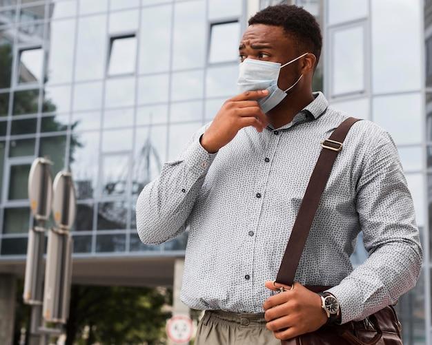 Стильный мужчина с маской на лице по пути на работу во время пандемии
