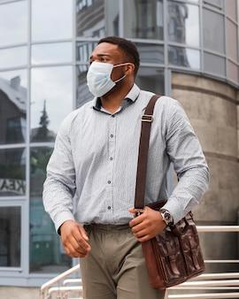 流行中に仕事に行く途中のマスクを持つスタイリッシュな男