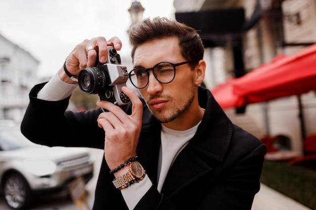 Стильный мужчина с фотоаппаратом делает фотографии в европейском городе.