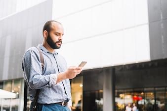 Stylish man with smartphone at street