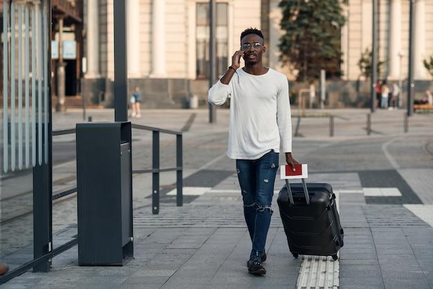버스 정류장에서 핸드폰으로 이야기하는 가방을 가진 세련된 남자