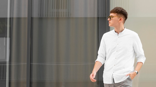 Uomo alla moda con occhiali da sole in posa all'aperto con spazio di copia