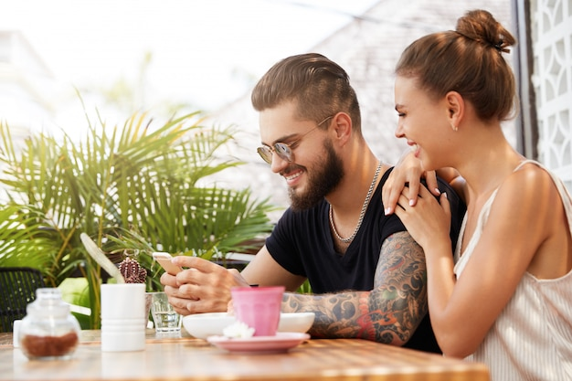 Stylish man and woman sitting in cafe