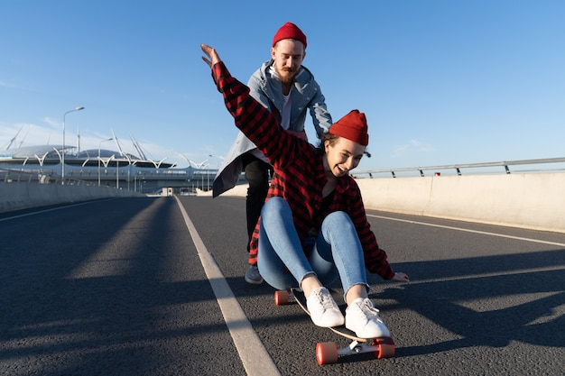 Stylish man and woman skating on longboard enjoy time together urban fashion and trendy activity