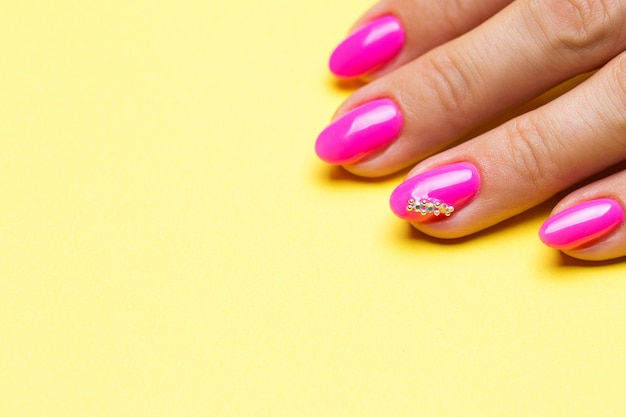 Stylish manicure pink on a yellow.