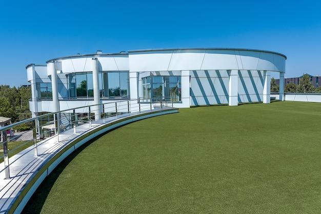 Стильный особняк с террасой на крыше первого этажа, покрытой зеленой искусственной травой.
