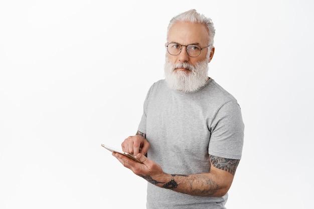 문신을 한 세련된 수염 난 남자, 안경을 쓰고, 디지털 태블릿을 사용하고, 진지한 정면을 바라보고, 회색 티셔츠를 입고 흰 벽에 서 있는