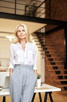 Стильная зрелая блондинка бизнес-леди смотрит в сторону, позируя стоя в офисе