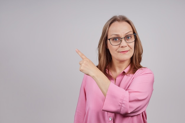 眼鏡をかけたピンクのブラウスのスタイリッシュな成熟した実業家は、彼女の手を横に保持します
