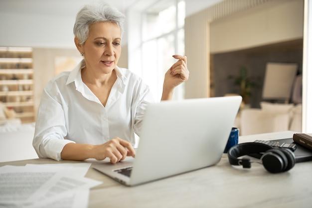 노트북 앞에 앉아있는 짧은 머리를 가진 세련된 성숙한 사업가, 마치 뭔가 말하는 것처럼 열린 입으로 화면을보고