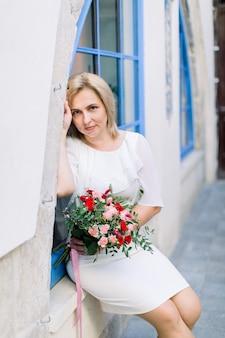 街の屋外の花の花束とカメラでポーズをとる白いエレガントなドレスのスタイリッシュな成熟した女性。背景に古代都市の青いヴィンテージウィンドウ。