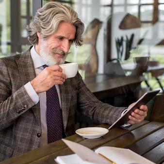 オフィスでスタイリッシュな成熟した男性閲覧テーブル