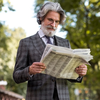 Stylish mature male reading newspaper