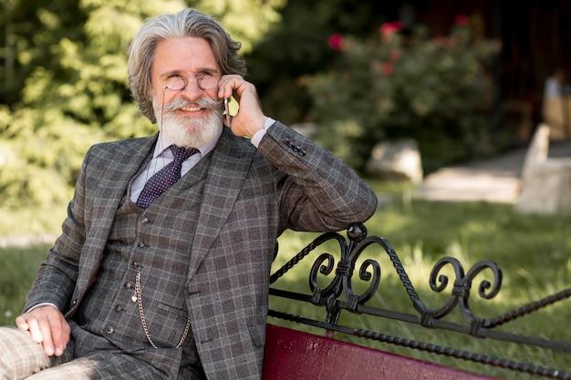 Стильный зрелый мужчина разговаривает по телефону