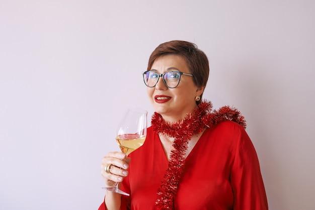 新年を祝う白ワインのガラスと赤いブラウスでスタイリッシュな成熟した年配の女性