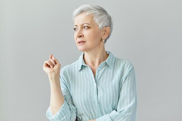 Стильная зрелая женщина-профессор или кушетка со стрижкой пикси смотрит в сторону, поднимает указательный палец, что-то говорит, читает лекцию, делится своим жизненным опытом.