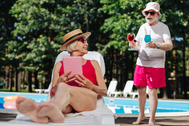 Стильная зрелая женщина в соломенной шляпе загорает у бассейна и читает электронную книгу