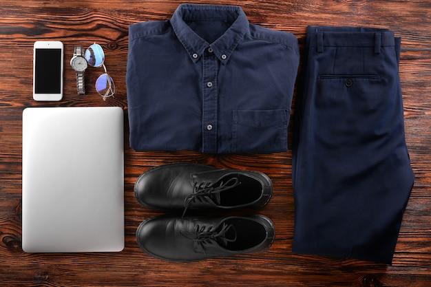 Стильная мужская одежда с аксессуарами и современными устройствами на деревянном фоне