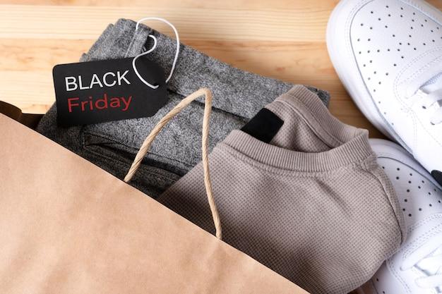 Стильная мужская одежда в бумажном пакете с обувью со знаком черной пятницы на деревянном столе.