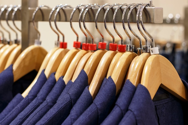 Stylish men's jackets on hangers in the store, close-up