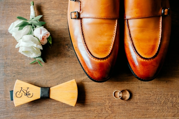 Stylish men's shoes on a dark wooden table next to the shoes is a , the groom is ready for the wedding