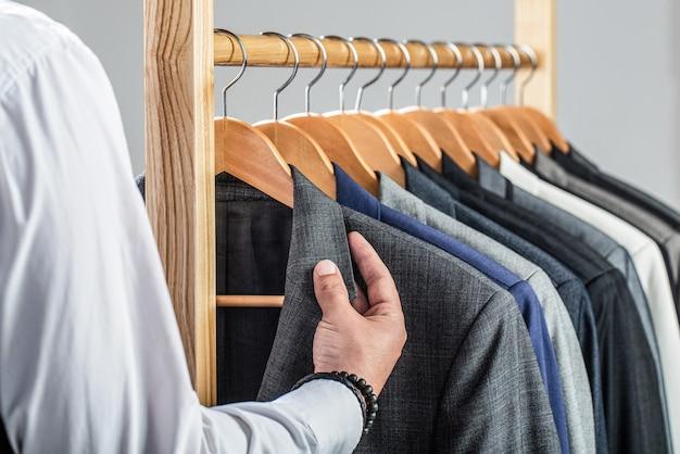Стильный мужской костюм. мужские костюмы висят в ряд.