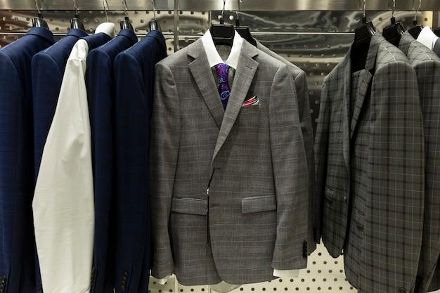 店内のスタイリッシュなメンズスーツ。エレガンスとファッション。閉じる。