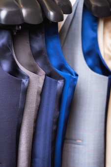 Stylish men's vest close up. male svest hanging in a row.
