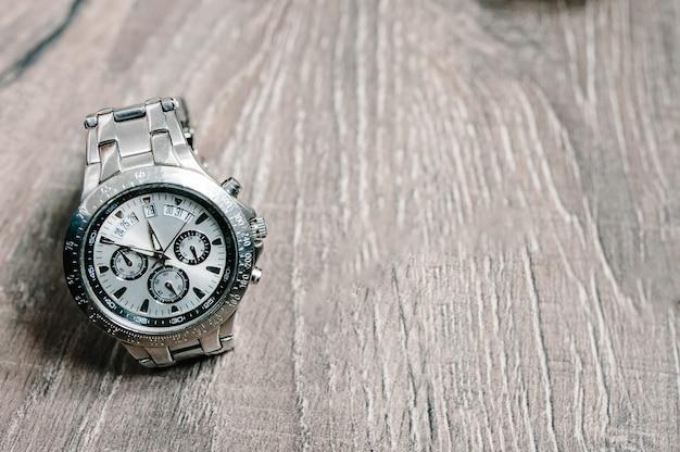 Стильные мужские часы, аксессуары, часы работы на деревенском коричневом деревянном фоне. вид сбоку. место для текста, дизайна и рекламы.