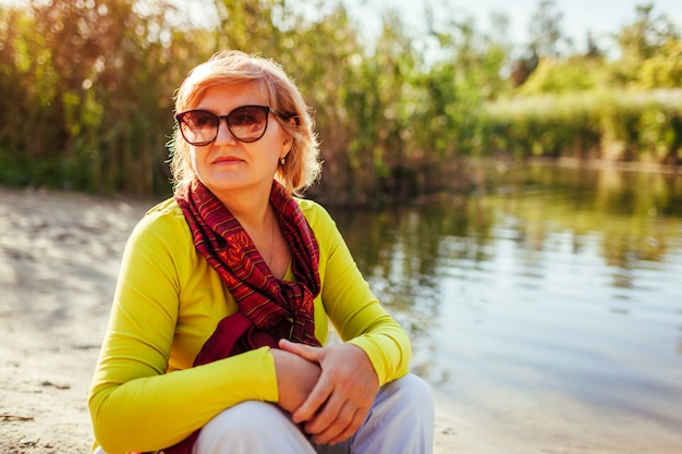 Stylish middle aged woman chilling by autumn river