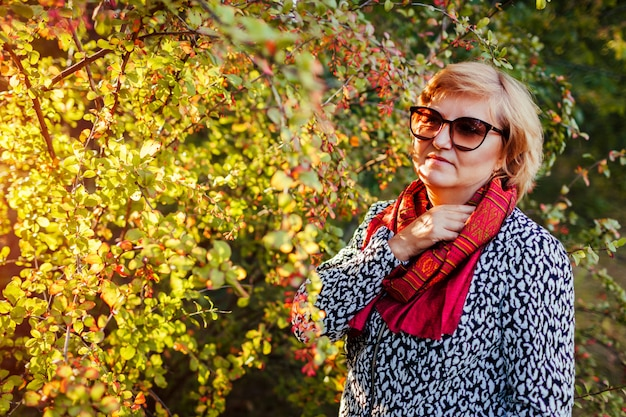 Stylish middle aged woman posing in autumn forest wearing fall clothes and accessories