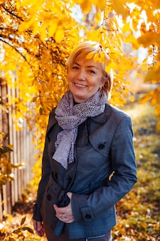 Stylish middle aged woman  wearing fall clothes and accessories in autumn park