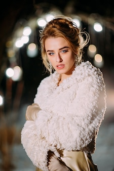 Stylish millennial girl in winter evening with lights