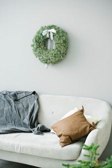 회색 벽에 베개가 달린 소파와 크리스마스 화환이있는 세련된 미니멀리스트 거실