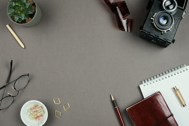 Copyspaceの灰色の背景にノートブック、プランナー、メガネ、ペン、ビンテージカメラでスタイリッシュなシンプルなモックアップ
