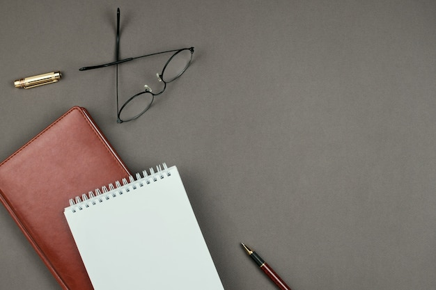 Stylish minimalist mockup with notebook, planner, glasses and pen on grey background on copyspace