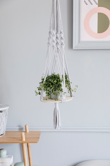 Stylish and minimalistic boho interior of living room with wooden shelf, design and elegant accessories, hand made macrame shelf planter hanger. botany and home decor with a lot of plants.